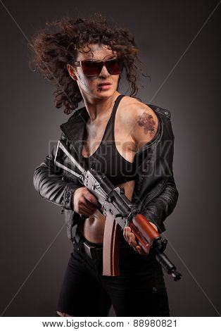 female killer with AK-74 (Kalashnikov) assault rifle in studio. With dirty face, blood and wound. poster