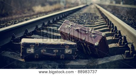 Two Vintage Suitcases Left On Railway Rails.