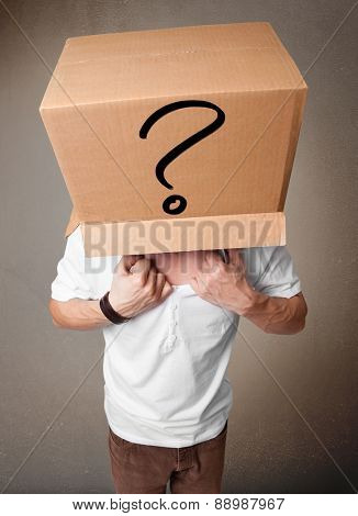 Young man standing and gesturing with a cardboard box on his head with question mark