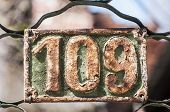 Old retro weathered painted cast iron plate with number 109 poster