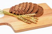 Slices of rye malt bread and wheat ears on the chopping board poster