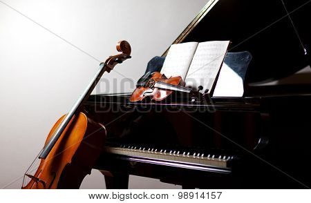 Classical music concept: cello and violin leaning on a piano