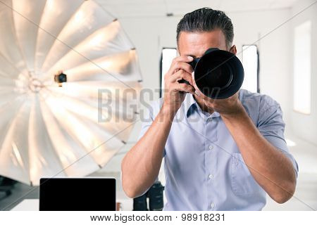 Photographer making photo on camera in studio