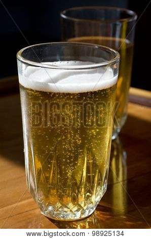 Two glasses of beer on wooden table