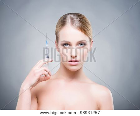 Attrative young woman injecting treatment into skin.
