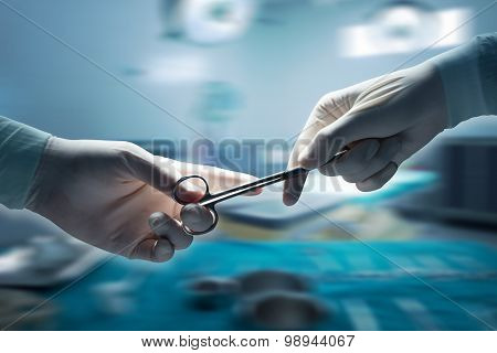 Close-up of surgeons hands hold equipment