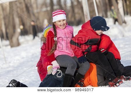 Children in winter park having fun and playing snowballs poster