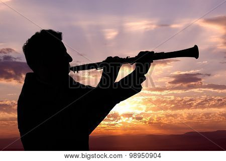 Trumpeter. Man playing on oboe against the background of sunset poster