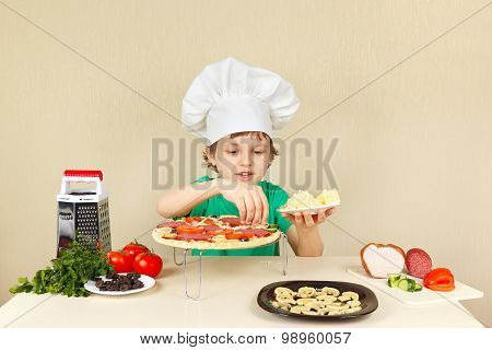 Young smiling boy in chefs hat puts a grated cheese on pizza crust