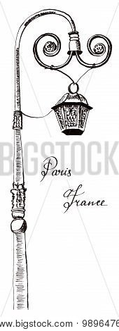 An ink drawing of a lamp post with the words 'Paris' and 'France' written in calligraphy on a white