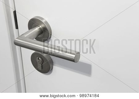 Metallic Doorknob With Lock Over A White Door