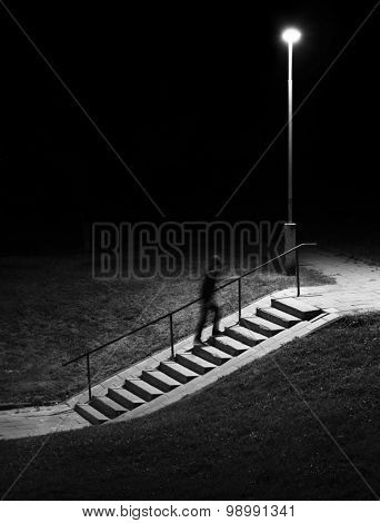 Night scene. Human figure in motion blur walking up stairs.
