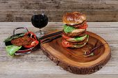 fresh grilled beef huge hamburger served on wood plate with red wine glass chili pepper rosemary green salad leaf and forged vintage antique cutlery over wooden table empty space for text poster