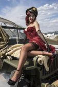 pinup dressed in era of the Second World War on a military jeep poster