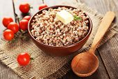 Buckwheat in bowl on brown wooden background poster