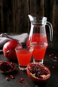 Pomegranate juice in glass and pitcher on black background poster