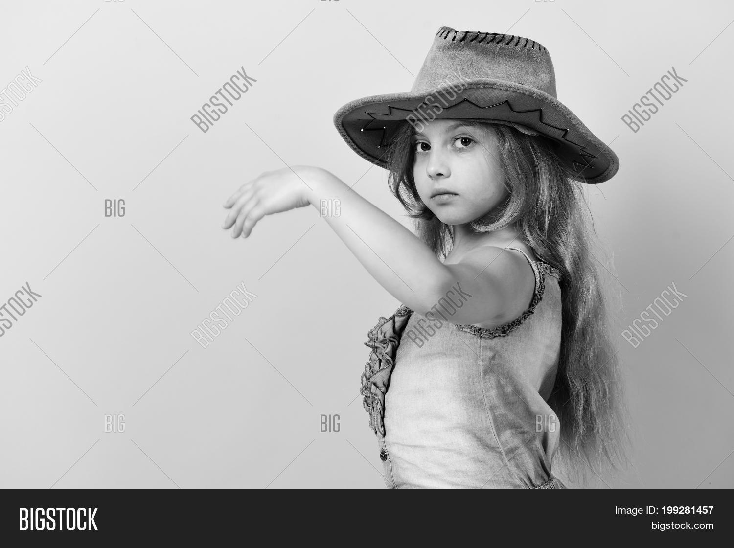 6bfc443e1e3ce Kid with serious face and long fair hair wears jeans dress. Fashion and  casual style concept. Girl in fancy outfit wears cowboy hat. Little lady in  stylish ...