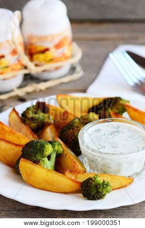 Home baked potatoes and broccoli with sauce on a plate and a wooden table. Vegan potatoes and broccoli recipe. Delicious vegetable lunch or dinner. Vertical photo