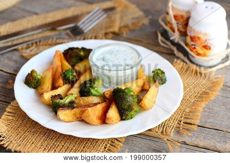 Golden baked potatoes and broccoli with sauce on a plate and a wooden table. Baked potatoes and broccoli recipe idea. Fork, knife, salt and pepper shaker on a vintage wooden background