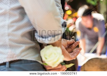 Focus the the Man hold the ring Men hide the ring and white rose behind with surprise.