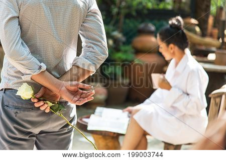 Man back and hand holding white rose with marriage ring making proposal of marriage Blurred girl sitting and reading a magazine.