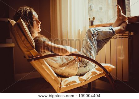 Thoughtful concept. Close up portrait sad woman lost in thought lounging in comfortable modern chair near window. Warm natural light. Cozy home. Casual style indoor. Room interior. Heating season