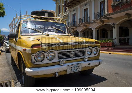 Granada Nicaragua - April 2 2014: Old yellow pick-up truck parked in front of a colonial building in the city of Granada in Nicaragua.