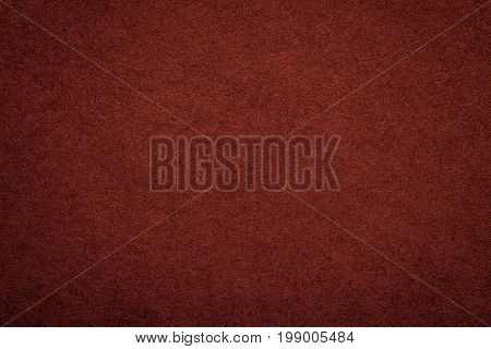 Texture of old dark red paper background closeup. Structure of dense maroon cardboard