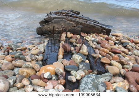 Waves crash over the wreckage of ship on the beach at Pictured Rocks National Lakeshore, Upper Peninsula of Michigan