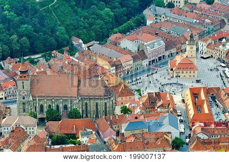 the central square of the old town. Brasov. Transylvania. View from above. The buildings the people. An interesting effect. Evening sunlight. Old Square people strolling on it an old clock tower