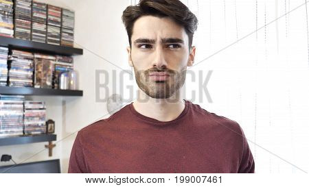 Confused or doubtful young man looking up. Indoors shot in a living room