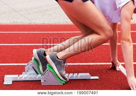 A high school female practice coming out of the blocks in track and field practice on a red track.