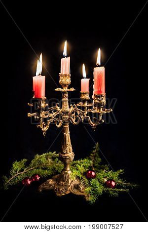 candlestick with five red burning candles on black background