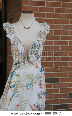 Vertical image of fashionable party dress and costume jewelry on mannequin outside shop