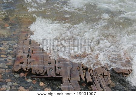 Wave washing over wooden wreckage of a shipwreck on a beach.  Pictured Rocks National Lakeshore, Upper Peninsula of Michigan