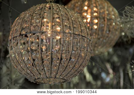 Two large crystal balls with soft lighting hanging in window