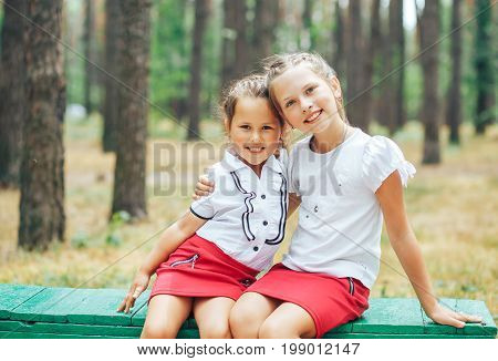 Two girls embracing each other sitting on a bench and smiling