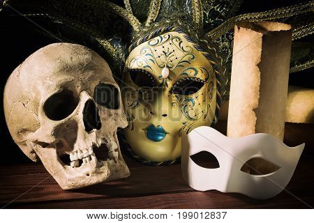Theater and drama concept. Human skull, venetian masks with old scroll on wooden table.