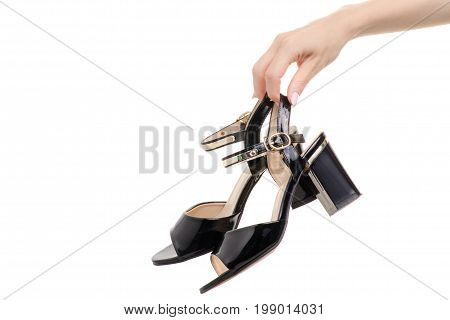 Black lacquer shoes in a female hand on a white background isolation