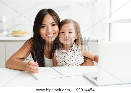 Image of happy young mom sitting at the table with little cute asian girl at home indoors using laptop computer writing notes to notebook. Looking camera.