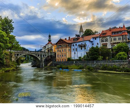 Beautiful sunset view of city of Murau with river, houses and church in Tirol, Austria, Europe.