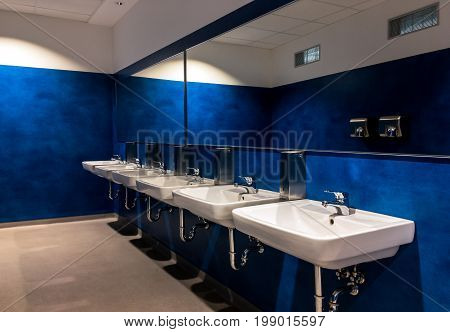 Six wash-basins in a modern blue restroom with large mirrors