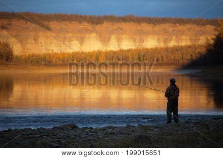 Evening fishing on the Siberian river autumn. A fisherman on the river at sunset. River Moiyero in the evening Evenkia Krasnoyarsk region