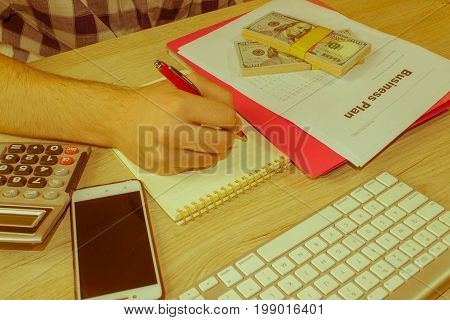 Close up view of bookkeeper or financial inspector hands making report calculating or checking balance. Home finances investment economy saving money - Retro color