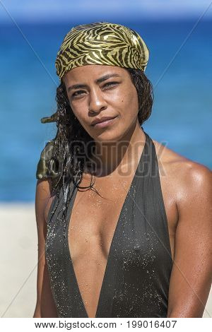 Portrait of young arab woman in swimsuit, wearing silk scarf and looking at camera, against sandy beach and blue sea.