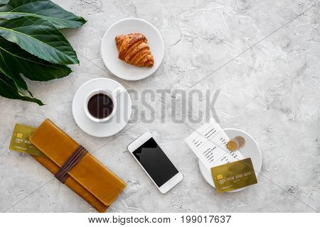 Pay bill at cafe by card. Purse, bill and bank card near coffee and croissant on grey stone table top view.