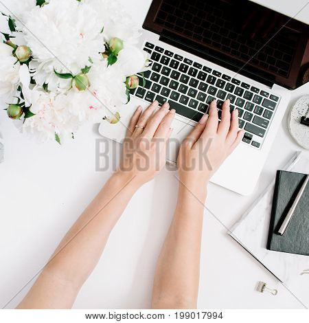 Flat lay home office desk. Women workspace with female hands laptop white peony flowers bouquet accessories marble diary. Top view feminine background. Girl working on laptop.