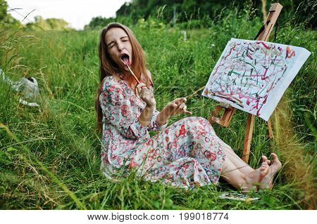 Portrait Of A Funny Girl Making Weird Facial Expressions While Painting On The Meadow.