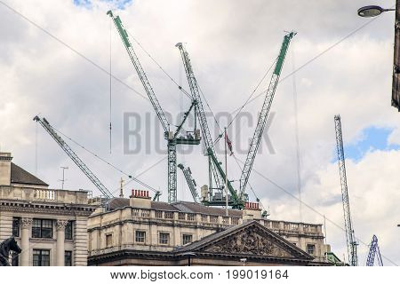 LONDON, GREAT BRITAIN - MAY 23, 2014: These are building cranes over the roofs of historic buildings which for many years are constantly building in the City of London.