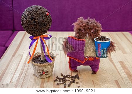 Handmade composition 'The money tree' made of coffee beans decorated with Ladybug DIY. Nearby stands owlet handmade and keeps the glass with coffee beans.